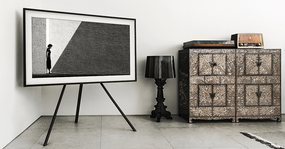 The Frame on a Studio Stand is next to the antique drawers and standing lamp. The Frame is on with art mode that makes the space more aesthetically.