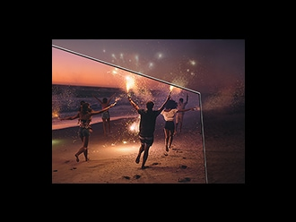 Image of people playing with sparklers on a beach at dusk.