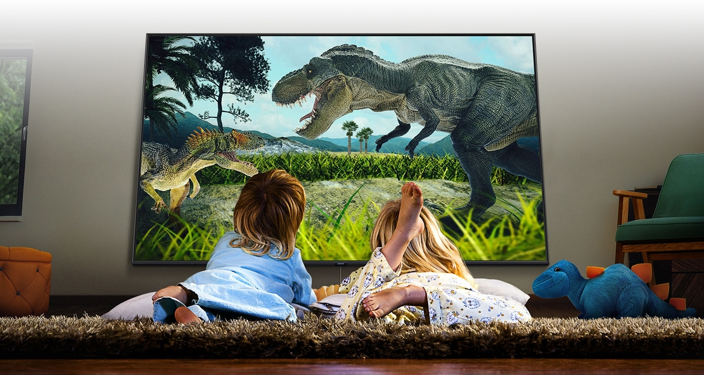 2 kids are watching a movie with lying down on the lug. The movie lively shows two dinosaurs fight.
