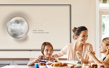 In a dining room, 4 people are enjoying their meals. Behind them, Super Big TV hung on the wall is showing weather forecast of the Ambient Mode.