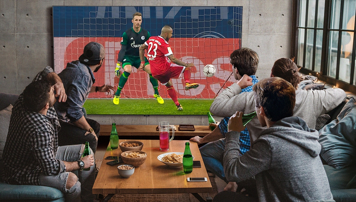 A group of five men sit around a coffee table while watching and cheering excitedly for a soccer game on a Super Big TV.