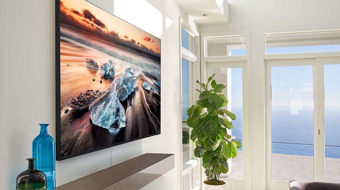 A lifestyle image of the 2019 new Samsung QLED Q900R. Image shows the side viewe of Q900R mounted on a wall over the fire place in the living room.