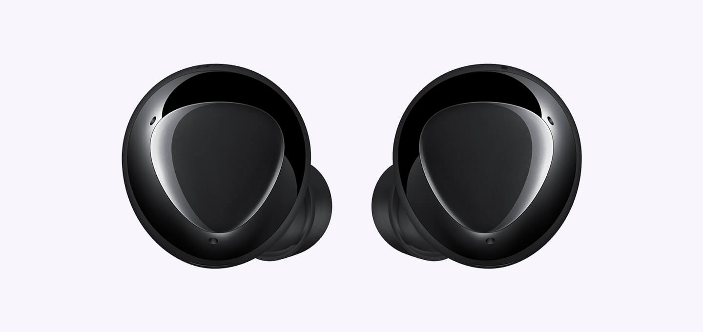 An enlarged pair of black earbuds displaying the triangular design on the outer surface.