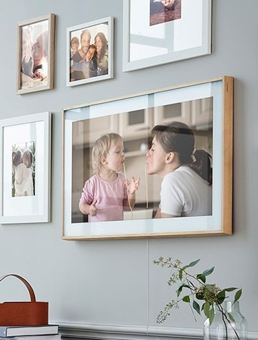 The Frame on the wall displaying a family photo among other picture frames.