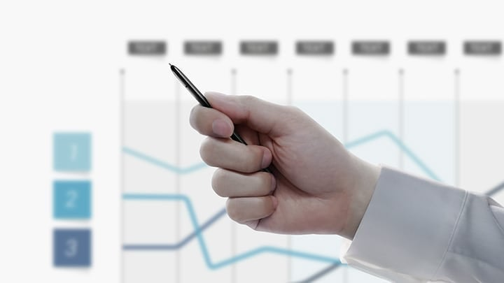 Simulated image of a person holding the S Pen with a presentation in the back showing a line graph. After the person clicks the S Pen button, the presentation slide switches to another graph.