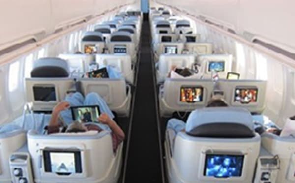An image showing some tablets in an airplane being operated by passengers
