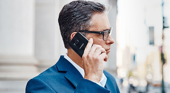 A businessman talking on a Samsung smartphone