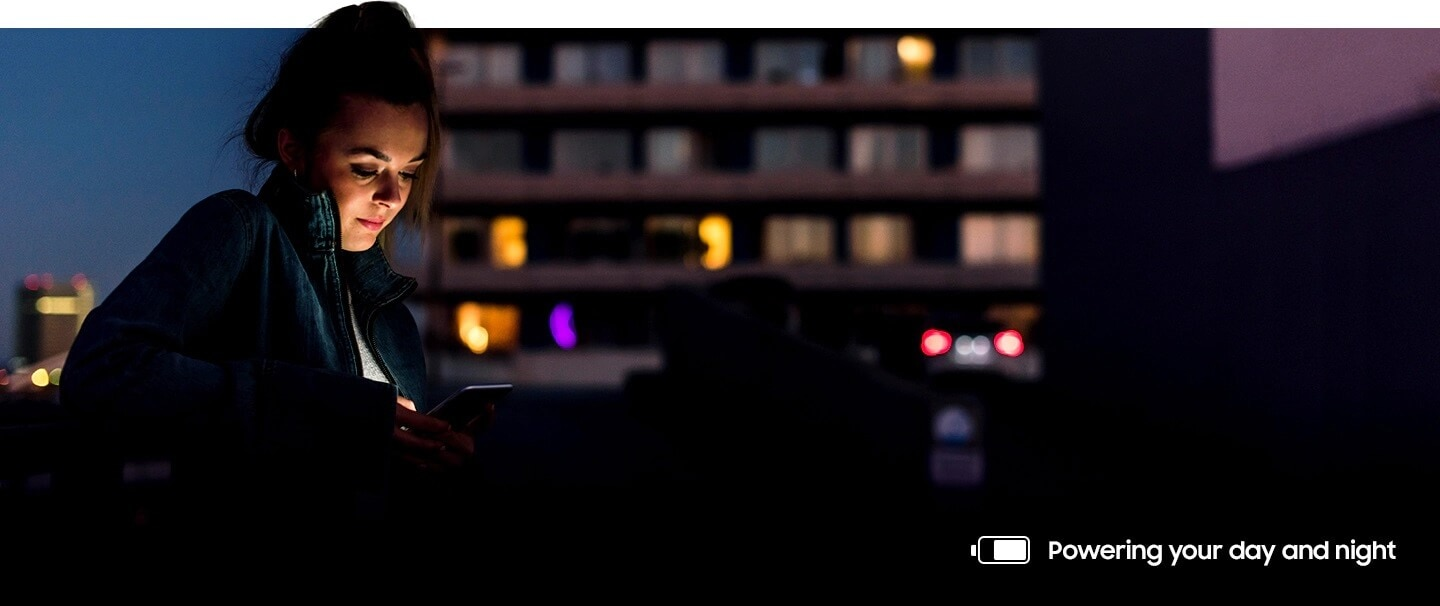 Image of a woman using her phone outside at night. A battery icon on the bottom right shows she has a most of her battery power left.