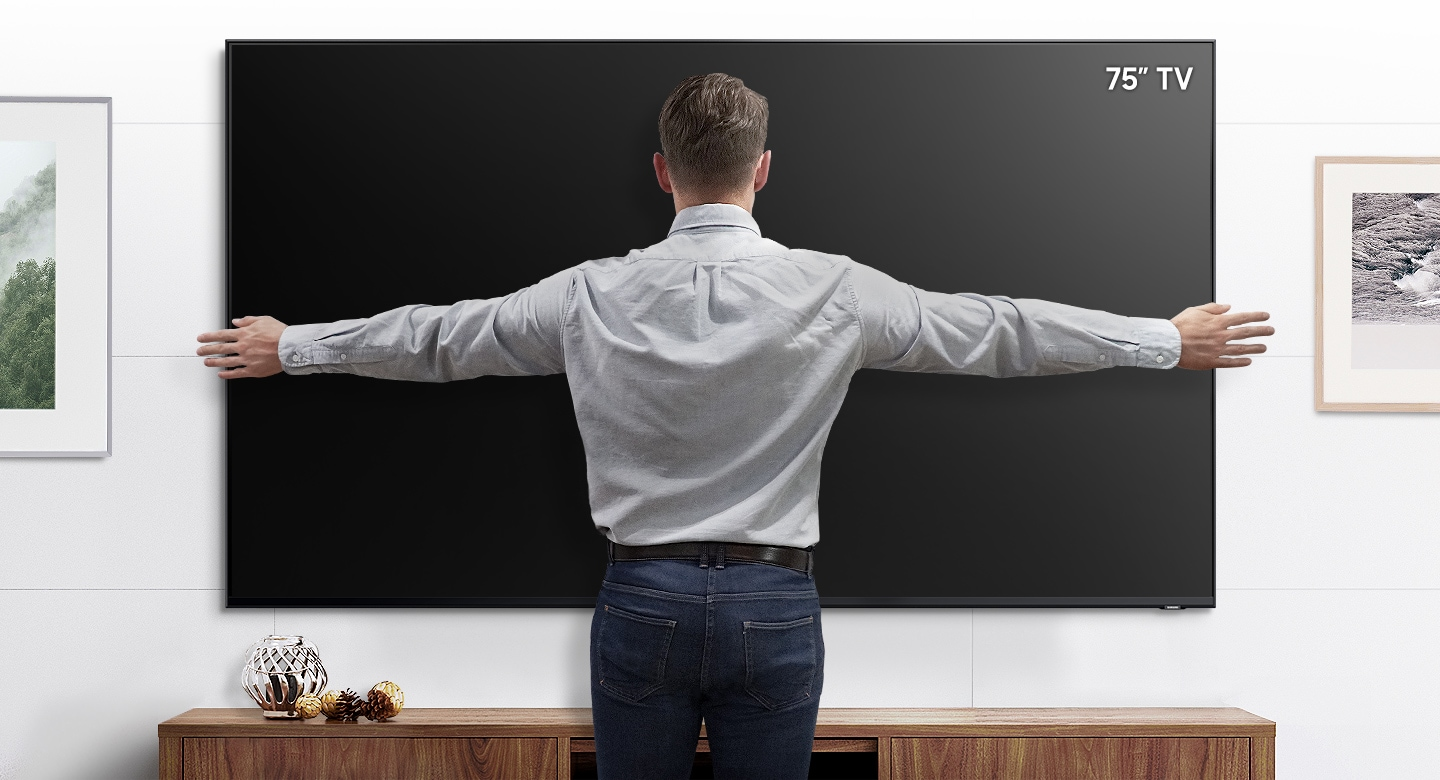 "A man stands in front of a wall mounted 75"" TV with his arms open to show that the TV fits within his arm span."