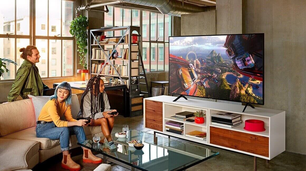 A lifestyle image of the 2019 new Samsung QLED Q60R. Q60R is put on TV table and two young people are watching it.