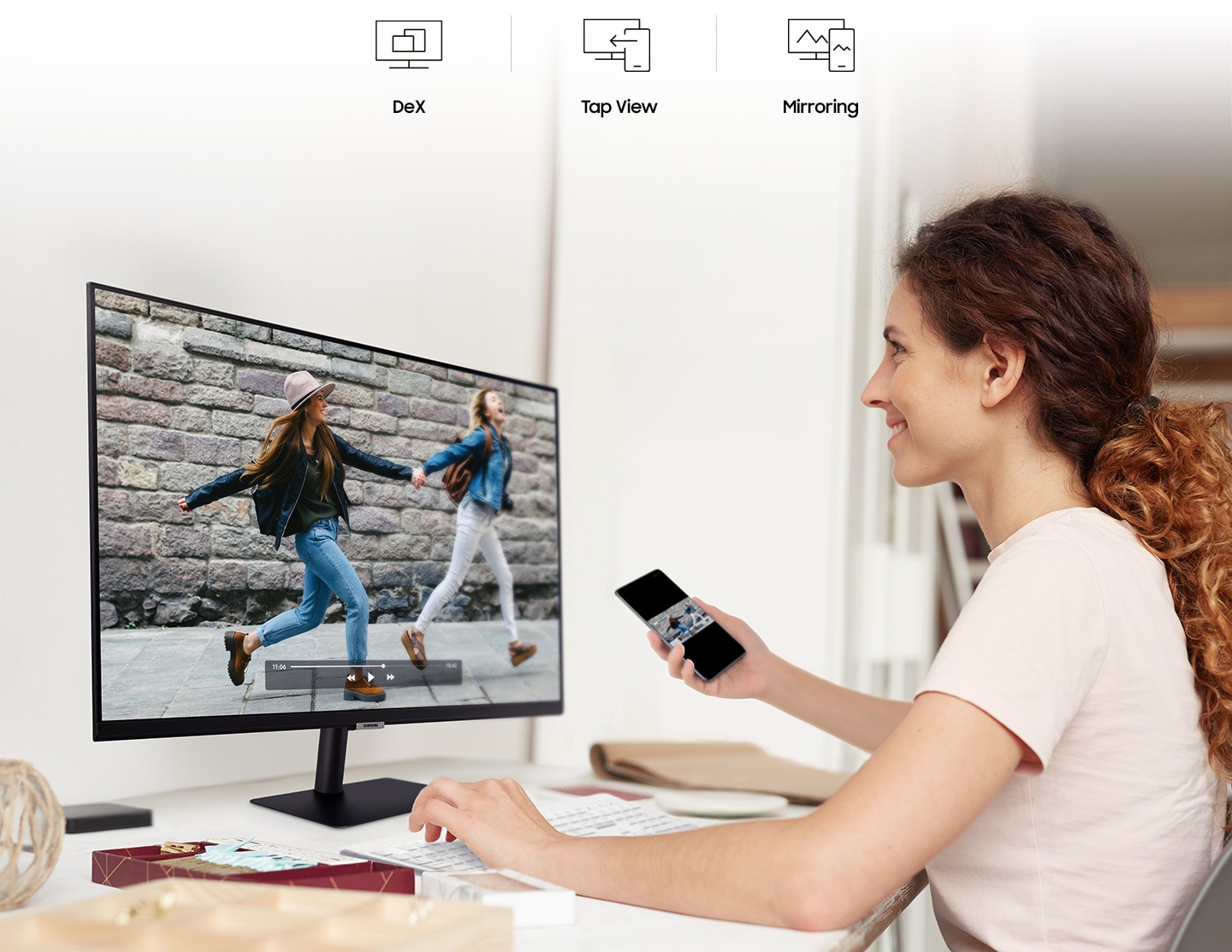A man connects a smartphone to his monitor using wireless DeX. A smiling woman mirrors videos from her phone to her monitor.