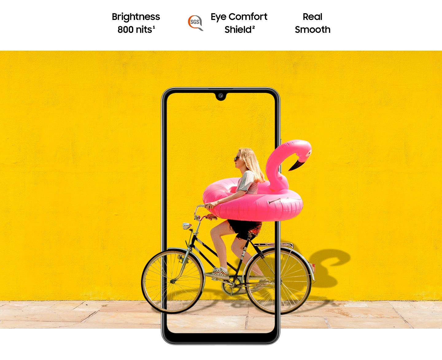 A woman on bike behind Galaxy A32. The picture goes the phone display's edges to represent its immersive view. Text says Brightness 800 nits, Eye Comfort Shield, with the SGS logo and Real Smooth.