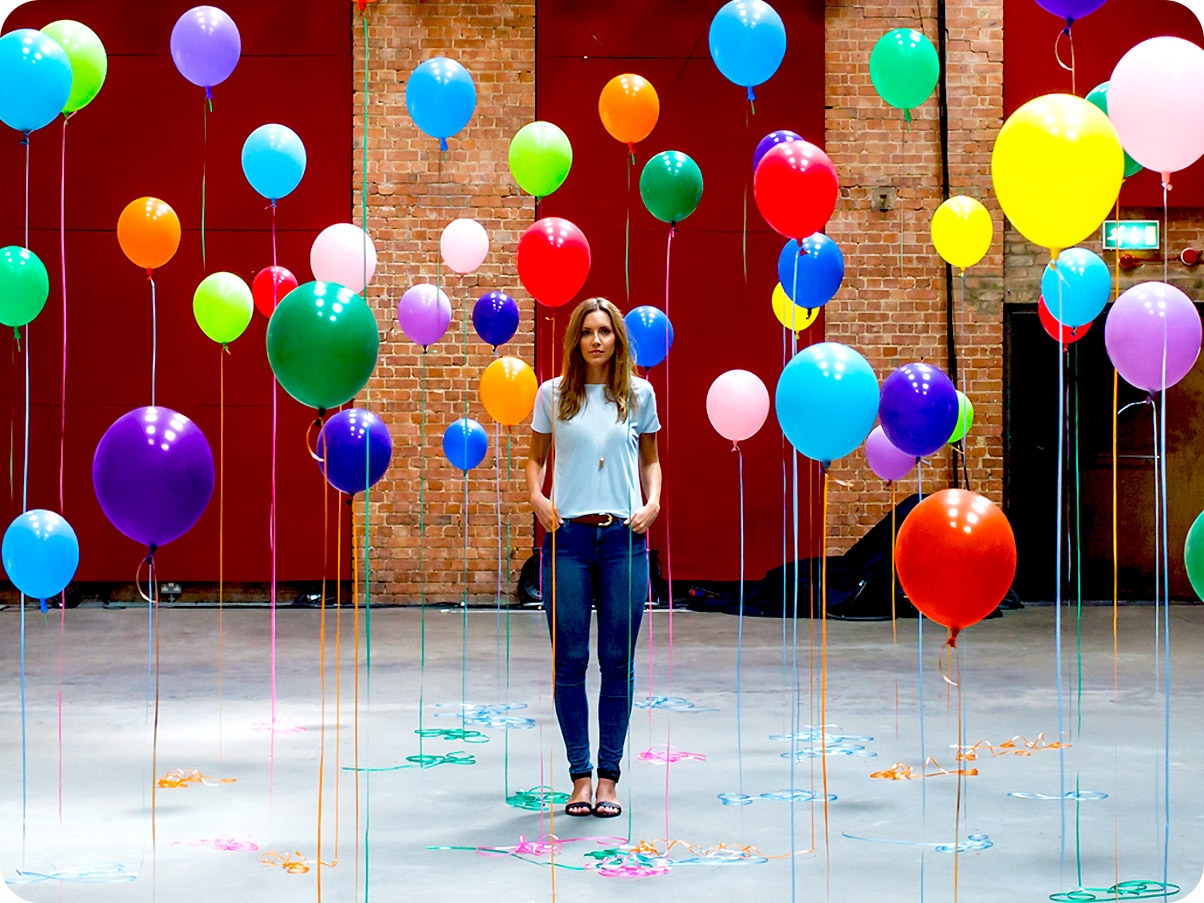 There is a close-up shot of a woman standing in the middle of many different colour balloons.