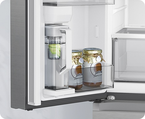 The fridge door is open to show the Autofill Water Pitcher filling with water, and with lemons in the built-in infuser.