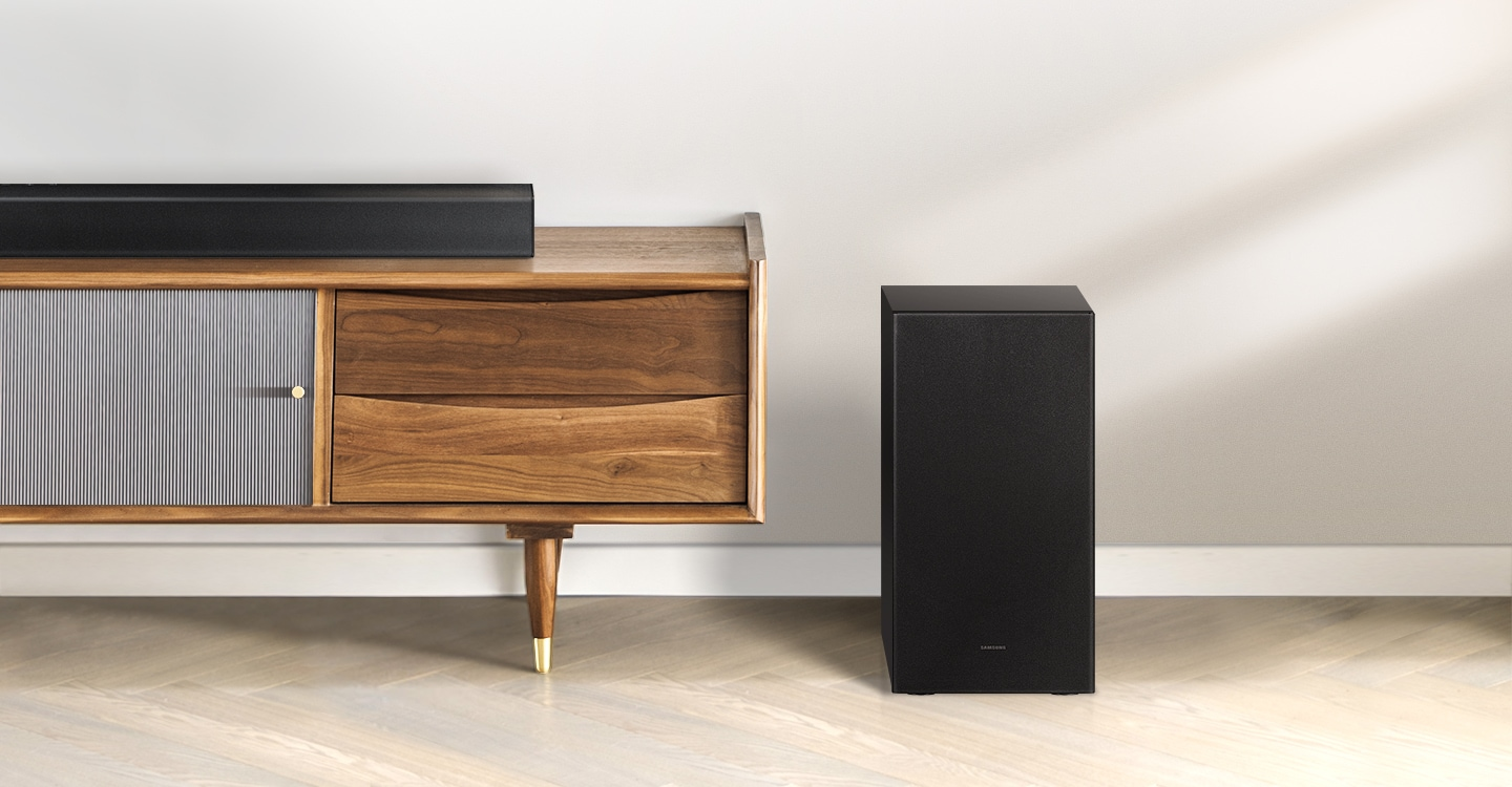 Samsung A series soundbar is being shown on top of a contemporary TV cabinet along with its matching subwoofer which is being displayed to the side of the TV cabinet.
