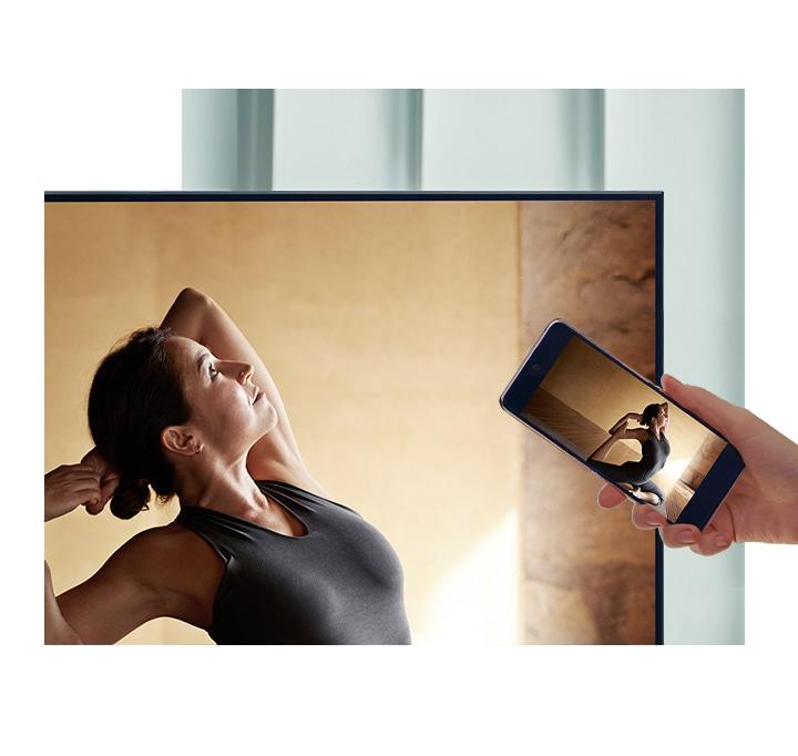 Uživatel klepne na svůj smartphone proti své QLED TV, aby zrcadlil svůj balerínový obsah na větší obrazovku pro větší pohodlí.