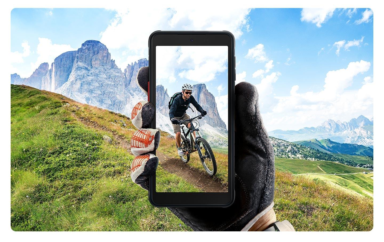 Ruka v černé kožené rukavici drží Galaxy XCover 5 a zobrazuje displej. Zachycuje osobu, která jezdí na cyklech, v pohledu na zelené hory a modrou oblohu.