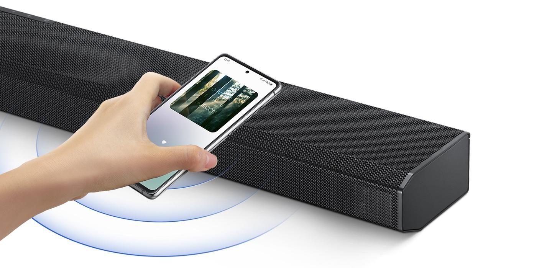 Ruka klepne na smartphone s hudební aplikací Samsung na obrazovce na soundbaru a soundbar okamžitě přehrává hudbu a ukazuje, jak snadné je přepnout ze smartphonu na soundbar.