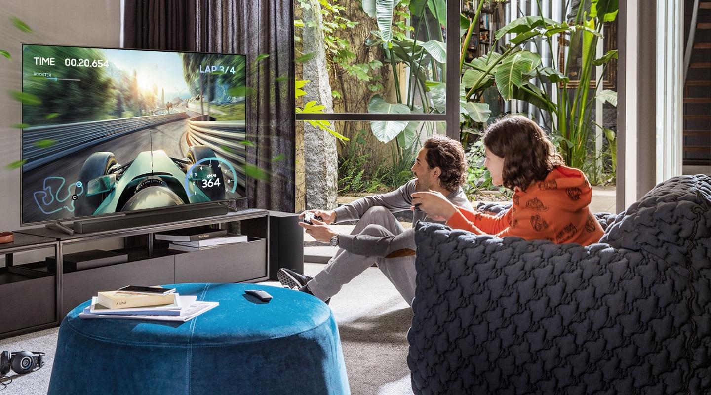 Dva přátelé si užívají pohlcující herní zážitek s herním režimem Samsung Soundbar Game Mode Pro.