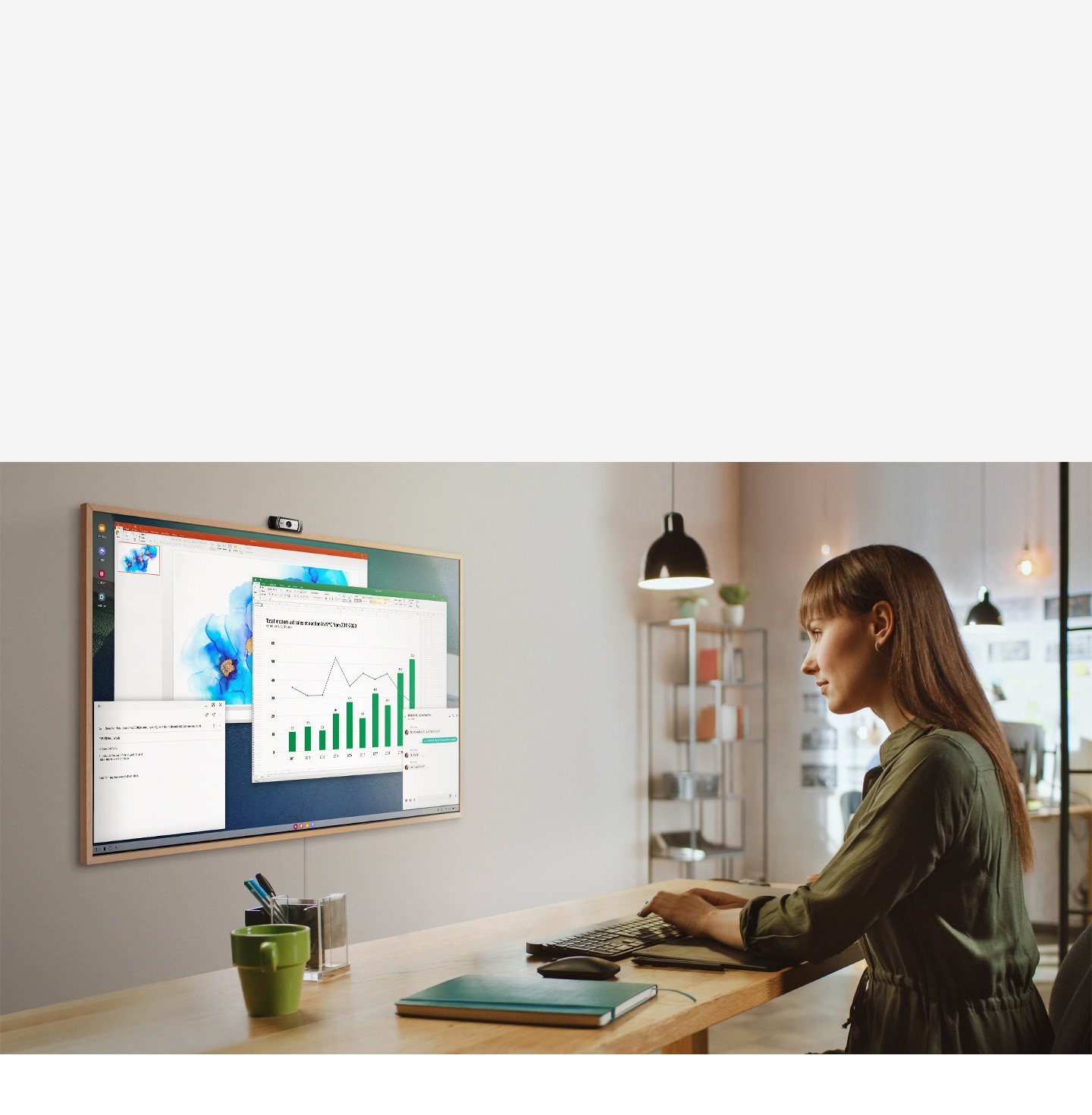 A woman is using her office PC to do work on her TV screen at home. On the screen of The Frame are various office productivity windows.