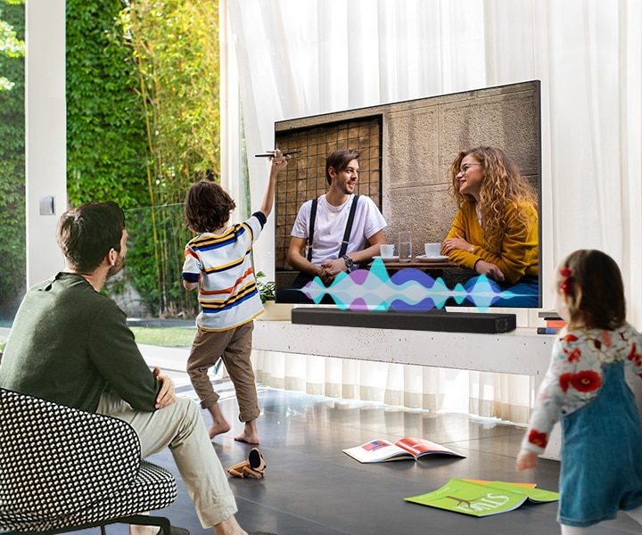 A man watches TV while his children play. Simulated sound wave graphics show Active Voice Amplifier technology optimizing dialogue so it can be heard more clearly in noisy environments.