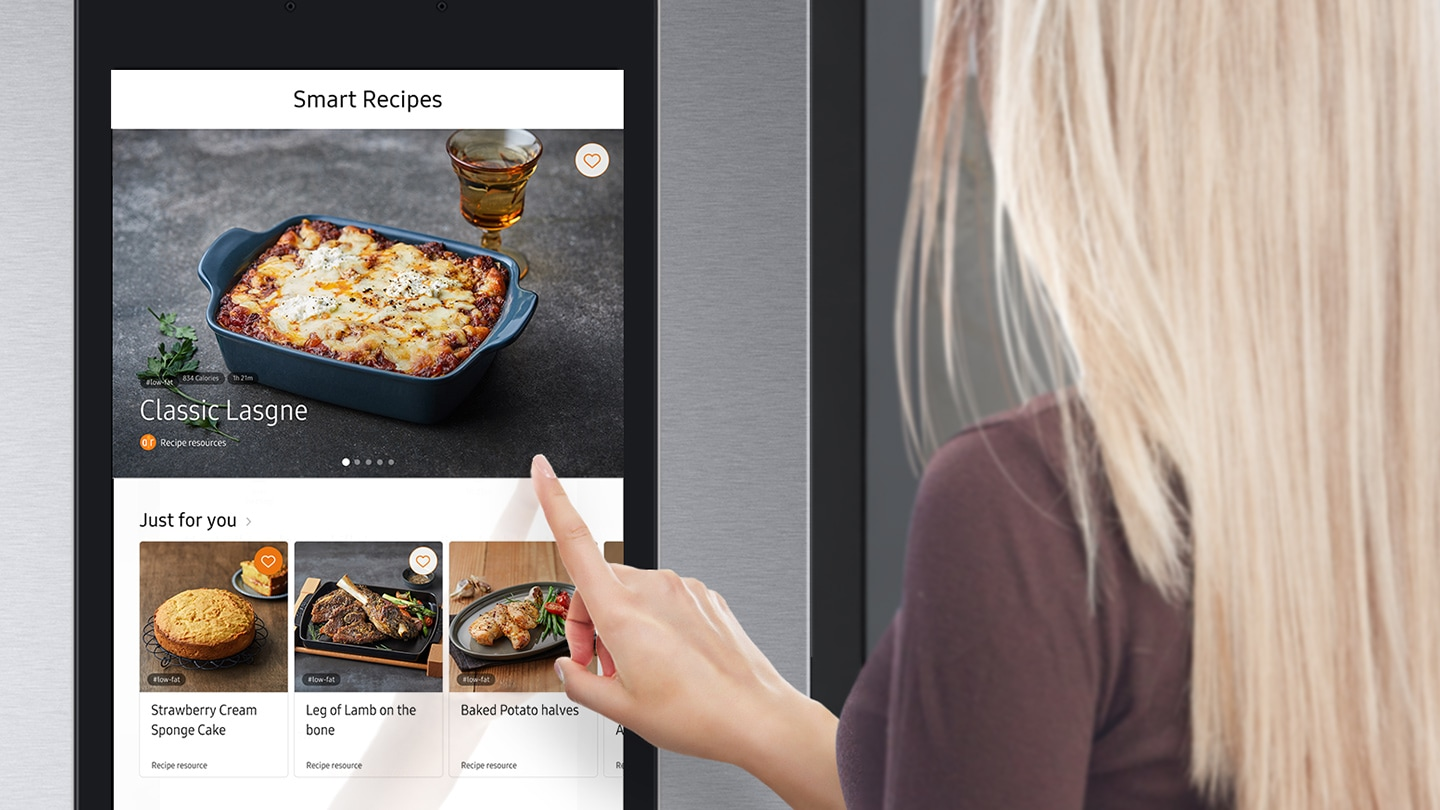 The woman is checking the recipes for the food with the Smart Recipes app on the Family Hub screen.