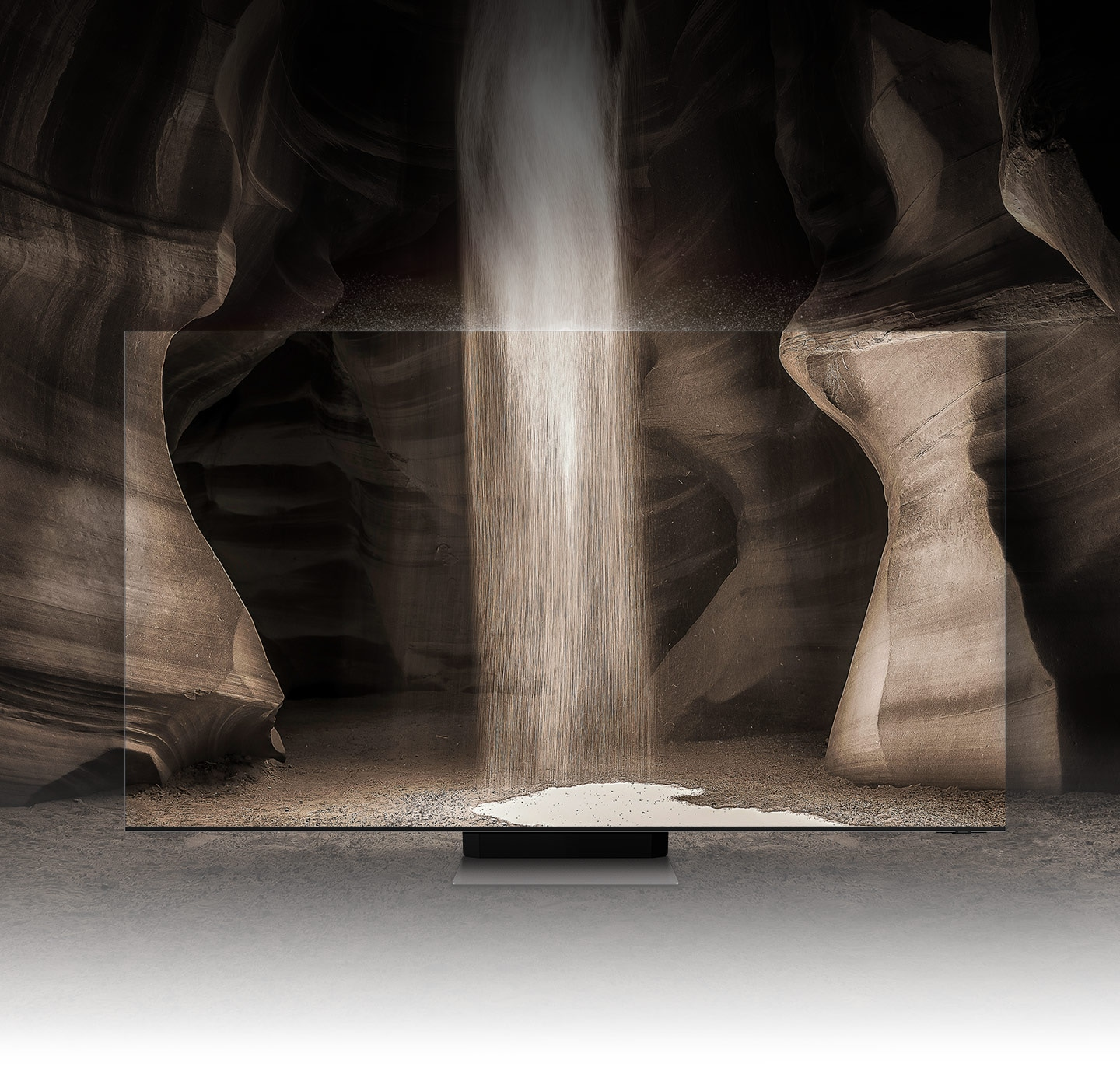 Somewhere in the cave, a QLED TV is placed, and sand falls from above. The edges of QLED TVs are so thin that it seems like there is no TV.