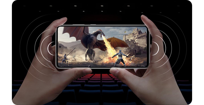 شخص يحمل Galaxy A72 في وضع أفقي مع وجود مشهد على الشاشة لفارس يحارب تنينًا ينفث النار، وموجات صوتية توضح مكبرات صوت ستريو.