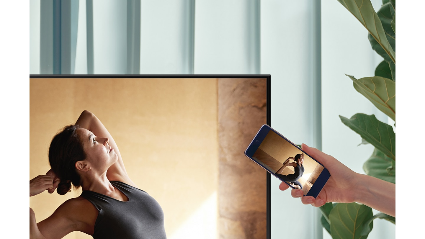 A user taps their smartphone against their AU9000 TV to mirror their ballerina contents to a bigger screen for more comfort.