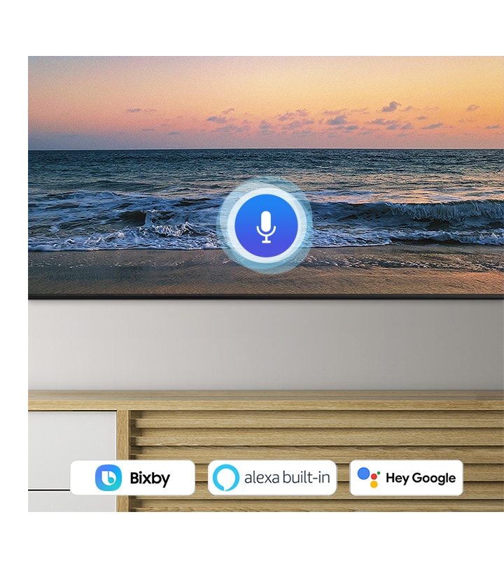 A microphone icon overlays a beach sunset TV screen image, demonstrating QLED TV voice assistant feature.