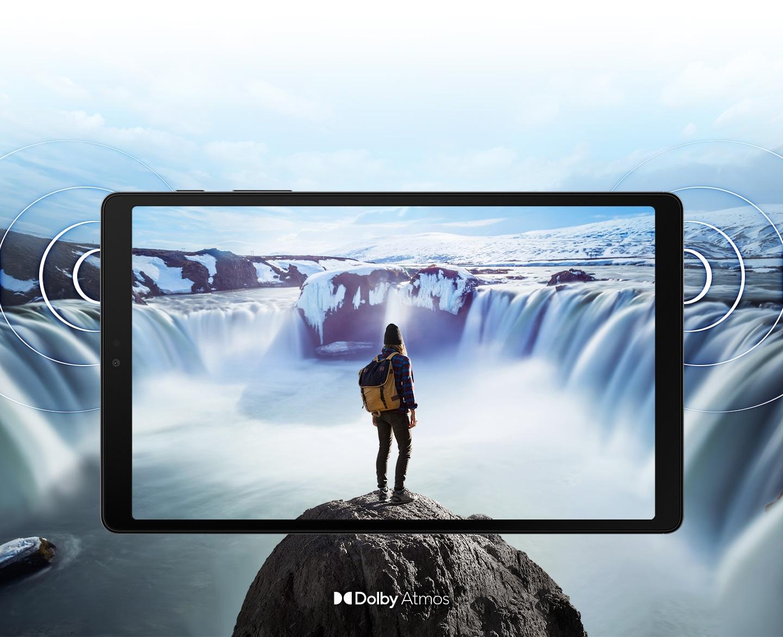 Galaxy A7 Lite visto desde el frente con una imagen de una persona parada sobre una roca frente a cascadas humeantes a ambos lados de la pantalla. La imagen se expande más allá de los bordes de la tableta para mostrar la amplitud de la pantalla. Los anillos salen de los lados para demostrar la ubicación de los altavoces duales y el sonido envolvente de Dolby Atmos.