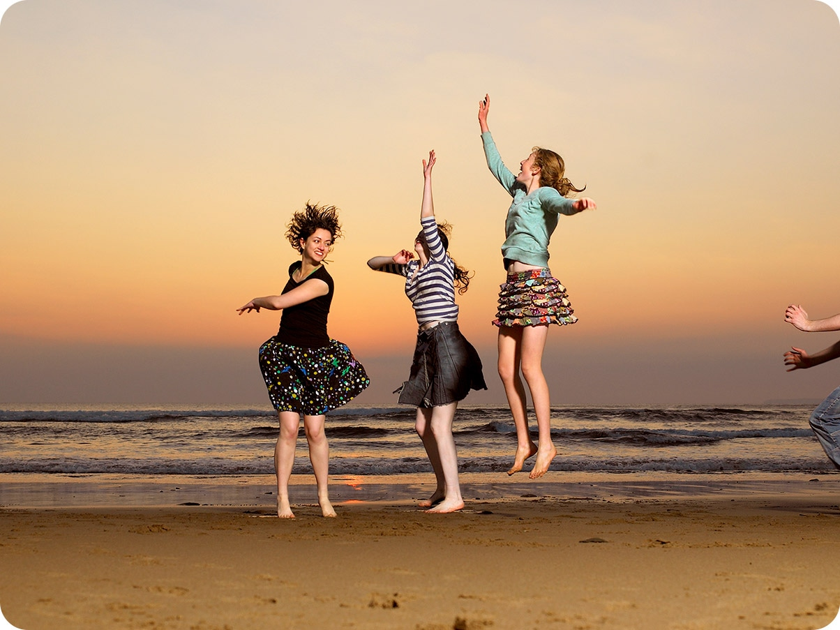1. Photo taken with Wide-angle Camera showing three women jumping on a beach at sunset.