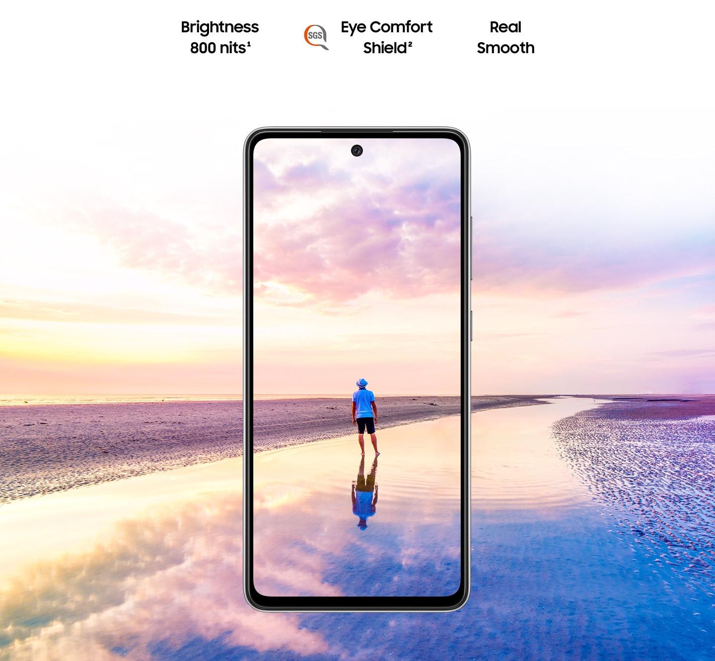 Galaxy A52 visto de frente. Una escena de un hombre de pie en una playa al atardecer con colores rosas y azules en el cielo, y que se expande fuera de los límites de la pantalla. El texto dice brillo 800 nits, Eye Comfort Shield, con el logo SGS y Real Smooth.