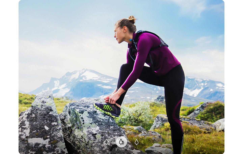 2.  Una mujer mirando a lo lejos con su pie sobre una roca y con menos partes de montañas mostradas en el fondo, lo que indica que el A72 puede capturar una imagen amplia con la Cámara Amplia.