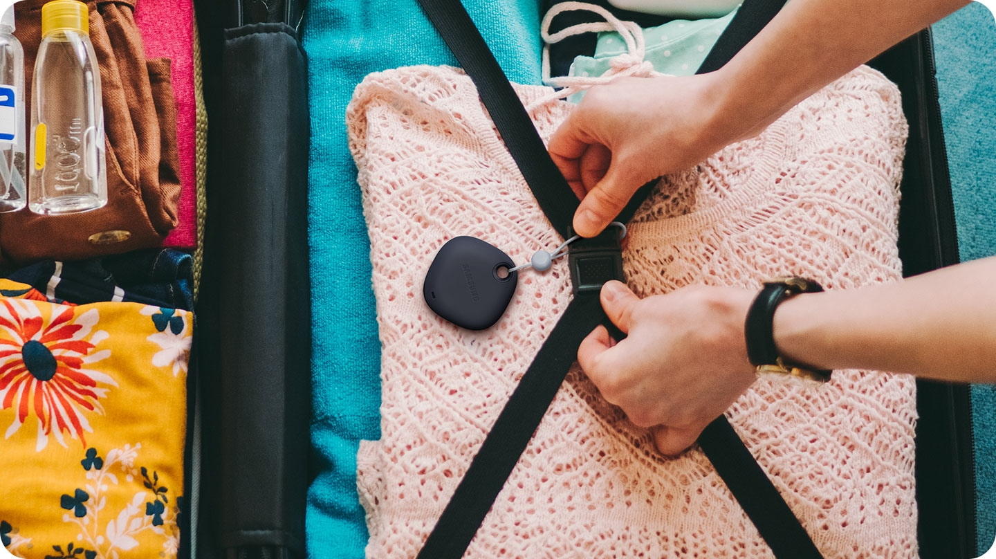 A person attaching a Galaxy SmartTag to the straps inside a suitcase, indicating SmartTag can be tied to important things