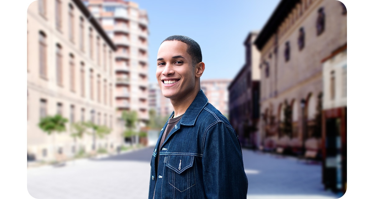 A man standing in a courtyard. Taken with the Depth Camera, the buildings in the background are blurred.