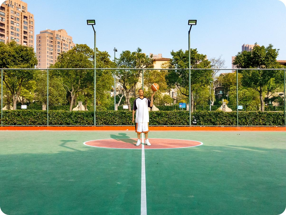 A man standing in a basketball court. Taken on the Ultra Wide Camera, you can see more of the court and scene around him.