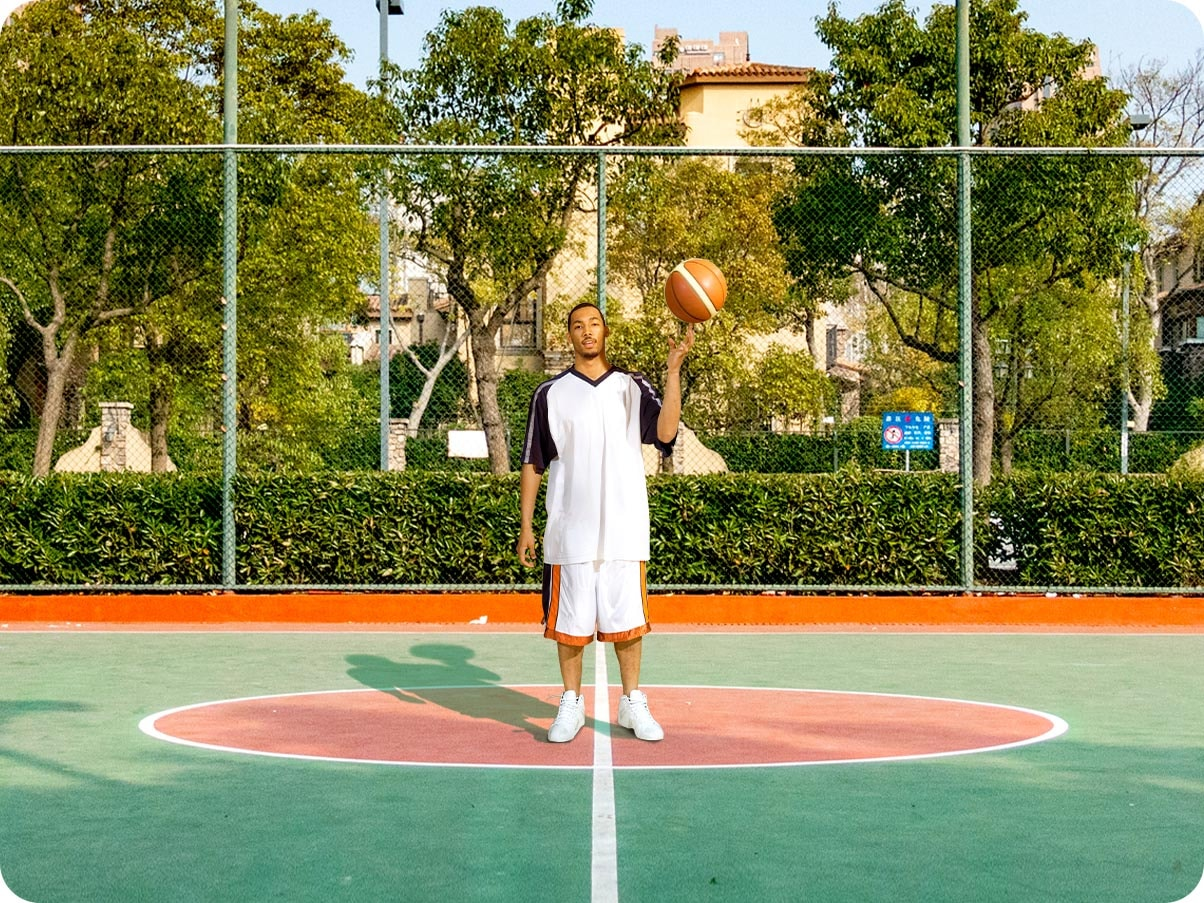 A man standing in a basketball court. It is a close crop shot, showing the man and the center of the court.