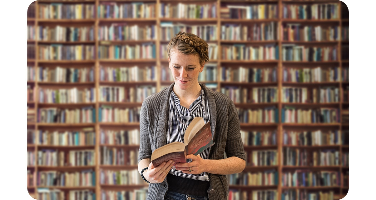 A woman reading a book standing in front of a bookcase full of books. The bookcase in the background in blurred out.