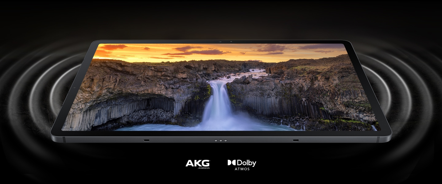 Galaxy Tab S7 FE seen laying on its back with a vivid scene of a landscape onscreen. On either side of the tablet are circles representing soundwaves coming out from the dual speakers, and showing the immersiveness of the sound. AKG logo and Dolby Atmos logo.