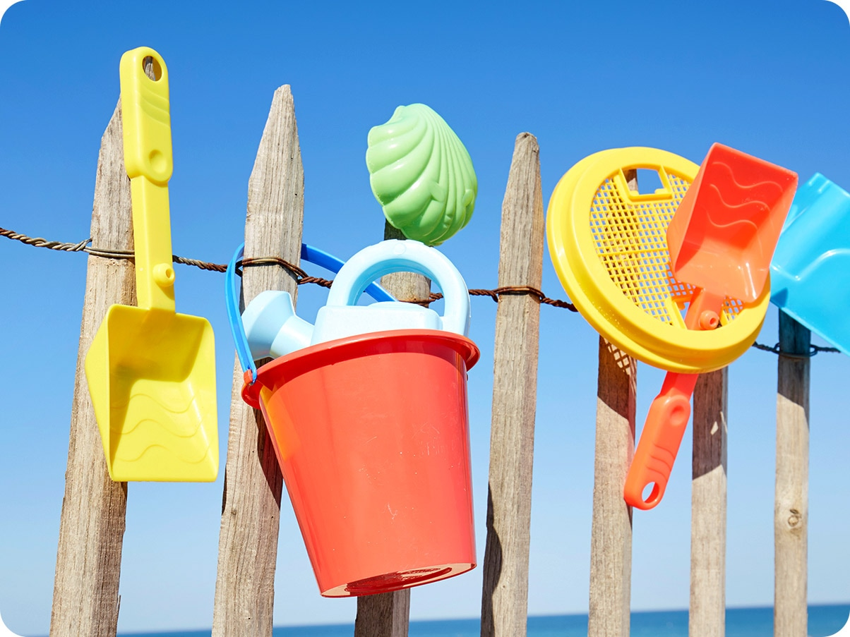 1. Beach toys are drying on a wooden fence.