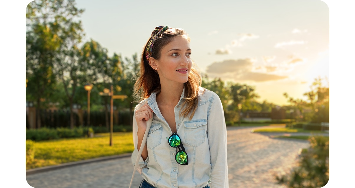 High quality portrait shot of a woman looking to the side, with grass patched road under clouds and sunlight in the background blurred out.