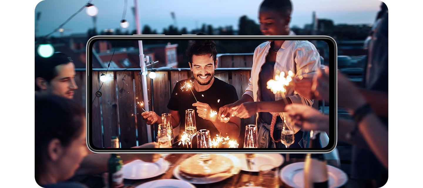 Galaxy A52 in landscape mode. Onscreen is a scene of people at a party in the evening playing with sparklers, and it expands outside of the display. The image inside of the display is brighter and more detailed than the portion outside of the display, demonstrating OIS.