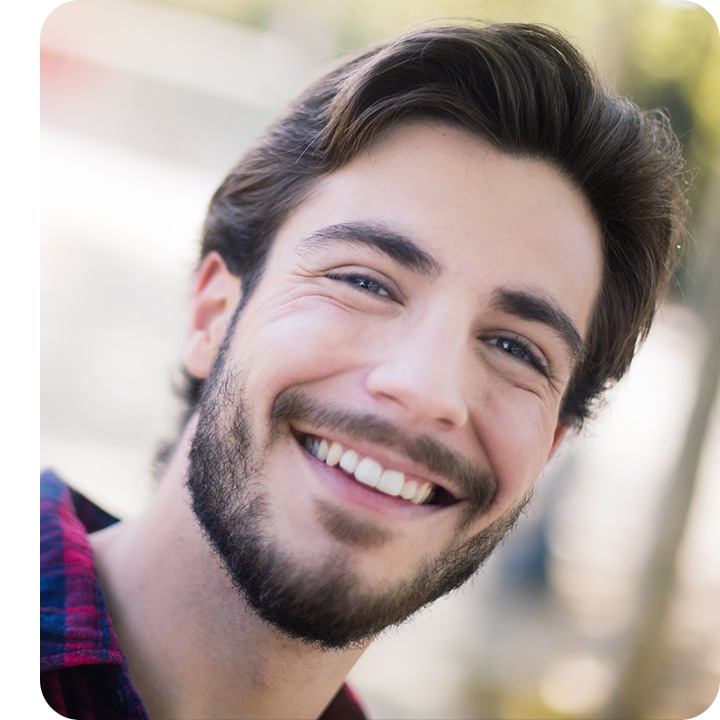 Selfie of a bearded man smiling and looking into camera lenses, with only a small part of blurred background showing.