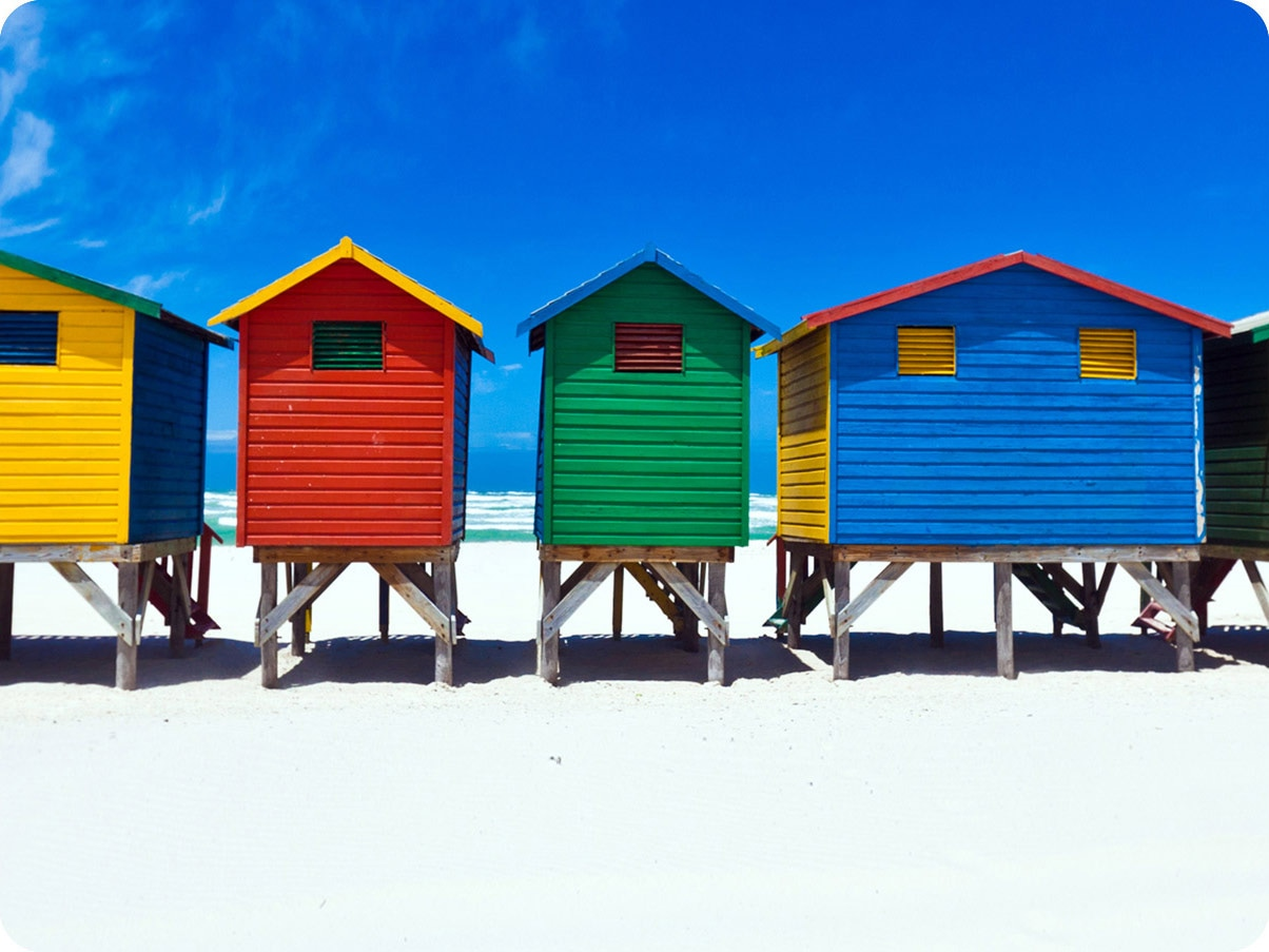The colorful houses are lined up with the blue sky. It is a close crop shot, showing the 4 colors (yellow,red,green,blue) of houses.