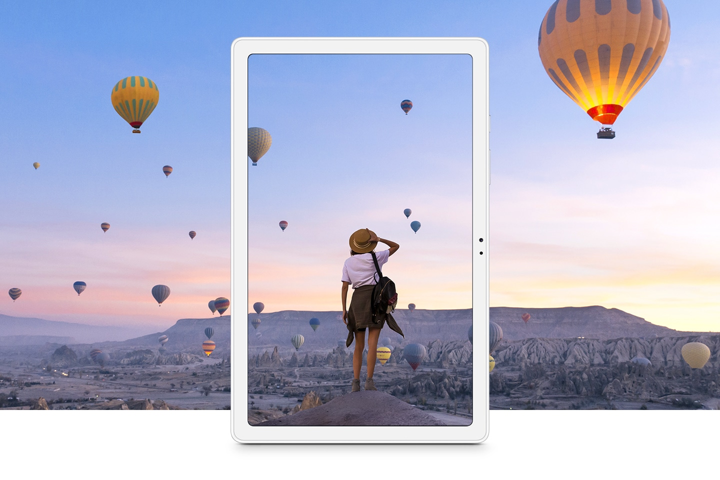 Galaxy Tab A7 depicts a woman overlooking a canyon filled with flying hot air balloons at dawn.