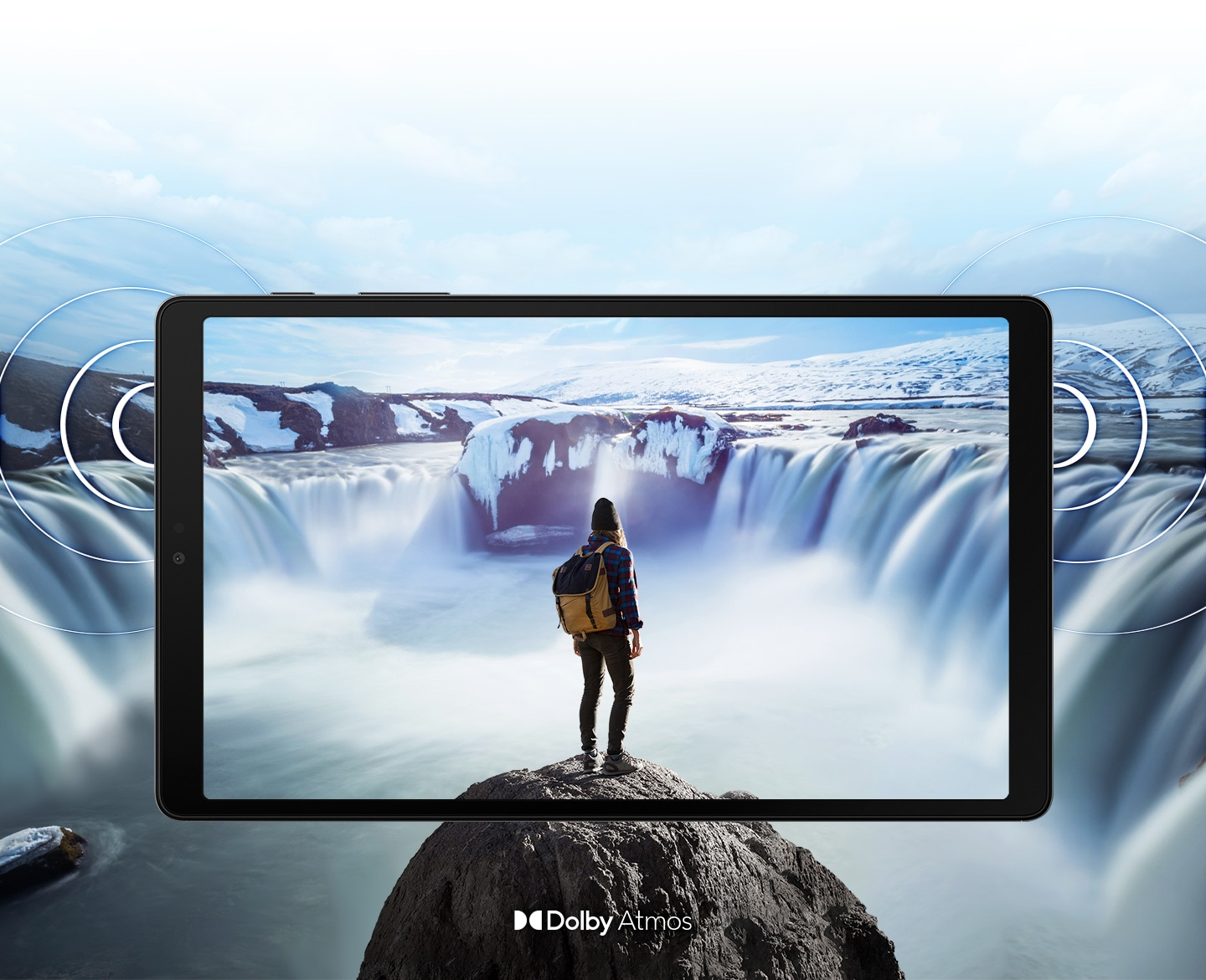 'Galaxy A7 Lite seen from the front with an image of a person standing on a rock in front of steaming waterfalls on either side onscreen. The image expands past the edges of the tablet to show the expansiveness of the display. Rings come out from the sides to demonstrate the location of the dual speakers and the immersive sound of Dolby Atmos.