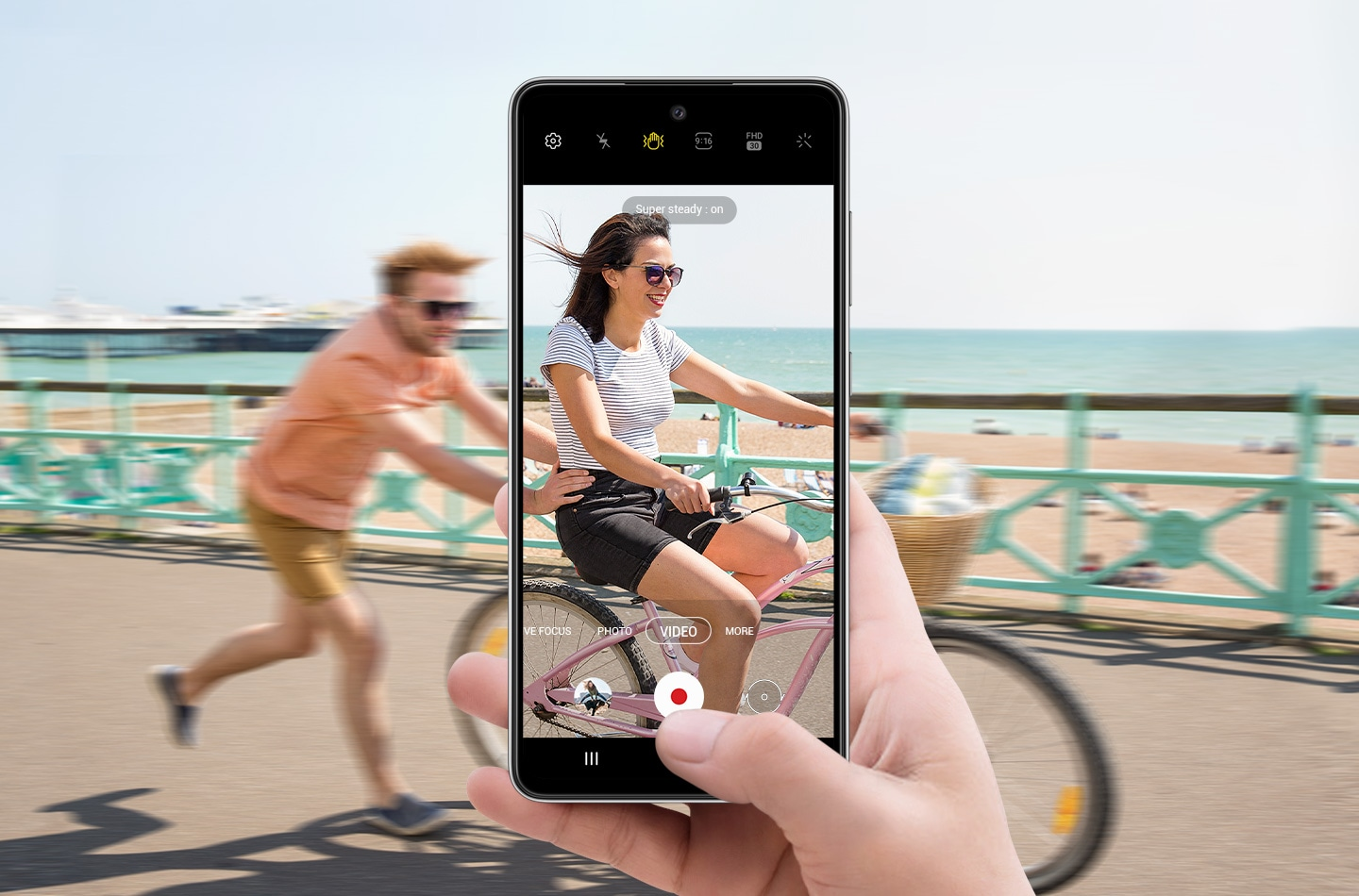 A person on a bike with another person running behind them and pushing. In front of this is a hand holding Galaxy A52s 5G with the camera interface onscreen. The scene in the display is clearer than the scene outside of the display, depicting how Super Steady allows video to be captured smoothly even if the subject is in motion.