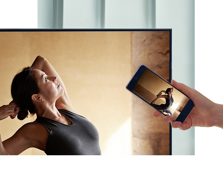 A user taps their smartphone against their AU7000 TV to mirror their ballerina contents to a bigger screen for more comfort.