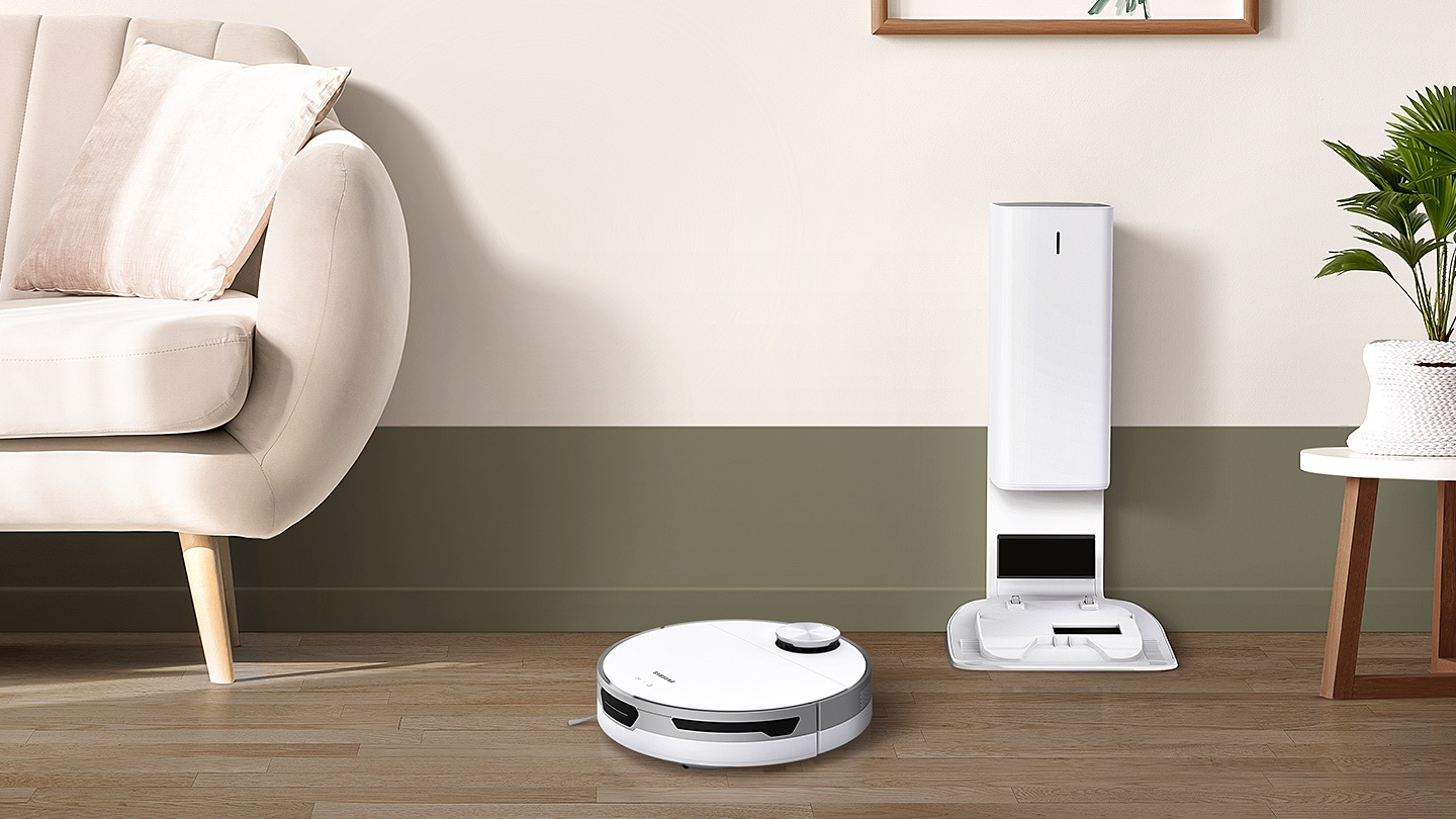 JetBot 80+ places itself between the sofa and plant, moving away from the cleaning station to clean the room.